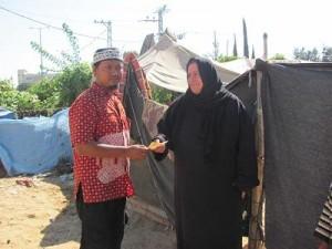 Fanni menyerahkan dana kepada pengungsi di tenda-tenda kamp Jabaliyah