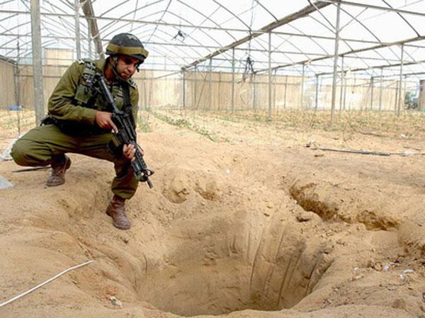 """Foto Ilustrasi dari """"Before It's News"""": Seorang serdadu zionis bergaya di atas mulut sebuah terowongan entah di mana."""
