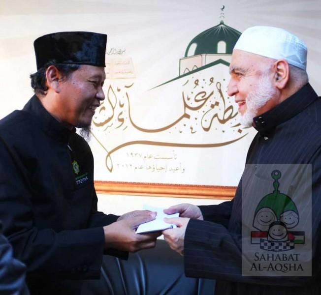 Dr. Muinudinillah Basri (kiri), Ketua Dewan Syariah Kota Surakarta, menyerahkan titipan masyarakat Indonesia untuk para 'ulama Syam diterima oleh Syeikh Usamah Ar-Rifa'i, Ketua Rabithah 'Ulama Syam. foto: Sahabat Al-Aqsha