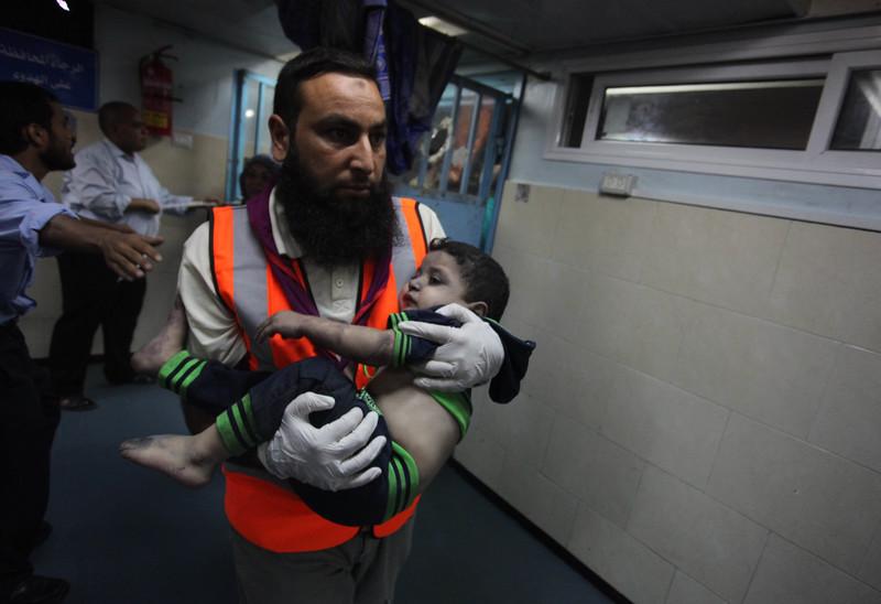 Petugas medis Palestina menolong seorang anak Palestina yang terluka akibat serangan udara Zionis 19 Agustus 2014 ke sebuah rumah di Kota Gaza yang menewaskan seorang gadis, seorang wanita dan melukai 16 orang lainnya. Foto: Ashraf Amra/APA Images