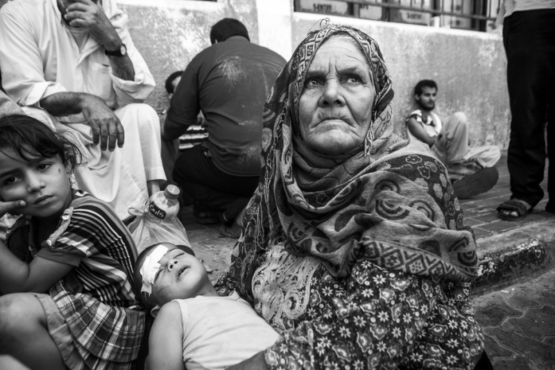Rizka Abu Rujeila, 70 tahun, memeluk cucunya di luar rumah sakit di Khan Younis, selatan Gaza pada 24 Juli lalu. Sang cucu terluka saat terjadi serangan di desa Khuza'a. Saat Zionis melakukan serangan darat sebagian besar penduduk desa itu berusaha mengungsi dan mereka diserang secara brutal saat coba meninggalkan desa. Khuza'a terisolasi selama beberapa hari. Tentara Zionis menghalangi pekerja medis dan jurnalis masuk. Sebagian besar penduduk mencari tempat perlindungan di rumah sakit, yang penuh sesak oleh korban tewas dan terluka.