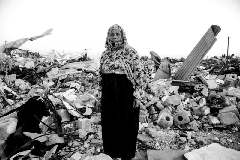 Salima Smeri, 62 tahun, pengungsi dan ibu dari enam anak, berdiri di tengah puing-puing rumahnya di desa Qarara pada 9 November 2014. Saat itu ia tinggal di tempat penampungan sementara. Pada Maret 2015, ia mendapat tempat penampungan baru yang terbuat dari kayu hibah dari sebuah badan amal. Namun, tempat itu tak dialiri listrik. Atapnya terbuat dari seng sehingga akan terasa sangat panas saat musim panas.