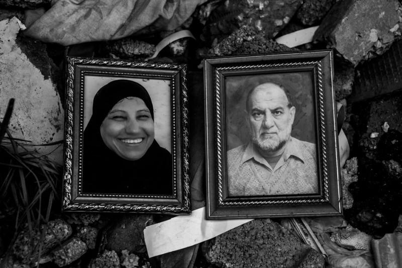 "Foto Ibrahim Abdallah Abu Aita (67) dan istrinya, Jameela Saleem Abu Aita (55) di reruntuhan rumah mereka di kamp pengungsian Jabaliya. Mereka terbunuh dalam serangan roket Zionis pada 23 Juli 2014. Pasangan itu tewas bersama dengan anak mereka, Muhammad dan Ahmad, serta cucu lelaki mereka yang berumur empat tahun, Adham. Mahmoud, anak Ibrahim dan Jameela yang selamat mengatakan, ""Berdasarkan apa yang saya lihat, saya pikir tak akan ada keadilan. Namun, saya tetap berharap mereka yang melakukan kejahatan itu akan mempertanggungjawabkan perbuatannya, terutama karena kami semua adalah rakyat sipil."""