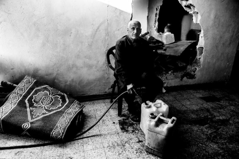 Seorang pria lansia Palestina sedang mengisi dirigen dengan air di rumahnya yang telah hancur di distrik Shujaiya, timur kota Gaza pada 4 September lalu. Seluruh bagian Shujaiya benar-benar hancur akibat serangan Zionis dan mengakibatkan ribuan warga Palestina kehilangan rumah mereka. Tak punya pilihan, sebagian besar kembali untuk tinggal di rumah mereka yang telah hancur parah dan tidak aman, serta tanpa saluran air dan listrik usai gencatan senjata.
