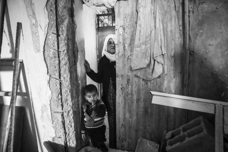 "Jamila Abu Odeh (umur tak diketahui) bersama cucu lelakinya di rumahnya yang telah hancur di Beit Hanoun. Ketika serangan Zionis tahun 2014, keluarganya mengungsi ke sebuah sekolah milik PBB. Keluarga ini kembali untuk menemukan rumah mereka yang hancur parah. Jamila mengatakan, ""Pada 1948, rumah kami dibakar. Namun, ternyata ada yang lebih buruk dari itu, yakni perang terakhir lalu.  Saya tidak akan melihat Palestina merdeka. Saya kehilangan semuanya."" Ibu dari sepuluh anak itu ditembak serdadu Zionis ketika ia tengah bekerja di ladangnya yang terletak di perbatasan antara Gaza dan 'Israel' pada tahun 2006. Akhirnya, ia kehilangan satu matanya. ""Saya bicara pada serdadu agar mereka berhenti membuldozer tanah saya, tapi mereka malah menembak saya,"" katanya."