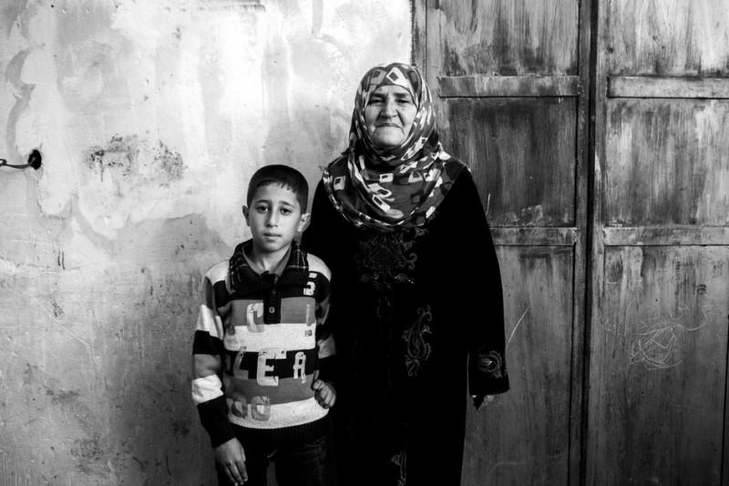 Naima, pengungsi berusia 74 tahun dari Bir al-Saba, dengan cucu lelakinya Ahmed Duhair. Seluruh keluarga dekatnya terbunuh ketika mereka kembali ke rumah mereka saat Idul Fitri usai menginap di rumah Naima selama dua minggu. Ketika keluarga itu kembali ke rumah mereka, Ahmed mendesak kembali ke rumah neneknya dan karena itulah ia selamat. Dua puluh satu anggota keluarga Duheir terbunuh, termasuk ibunda Ahmed, Jamalat (putri Naima), ayahnya Mahmoud dan lima saudara lainnya. Suami Naima ditangkap dan dibunuh saat intifada pertama.