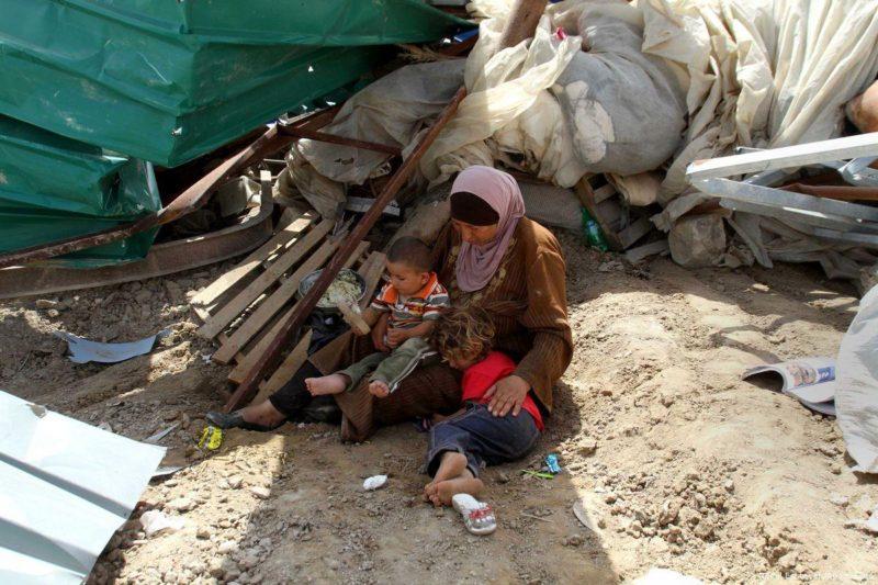 Seorang wanita Badui Palestina dan anaknya duduk di samping reruntuhan rumahnya yang dihancurkan oleh buldozer penjajah Zionis. Foto: Nedal Eshtayah/Apaimages