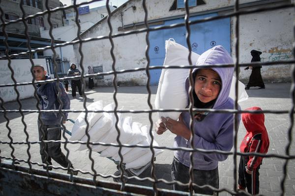 Para pengungsi Palestina mengambil paket bantuan di pusat distribusi makanan PBB di Rafah, bagian selatan Jalur Gaza pada 21 Januari 2018. Foto: Abed Rahim Khatib/Flash90