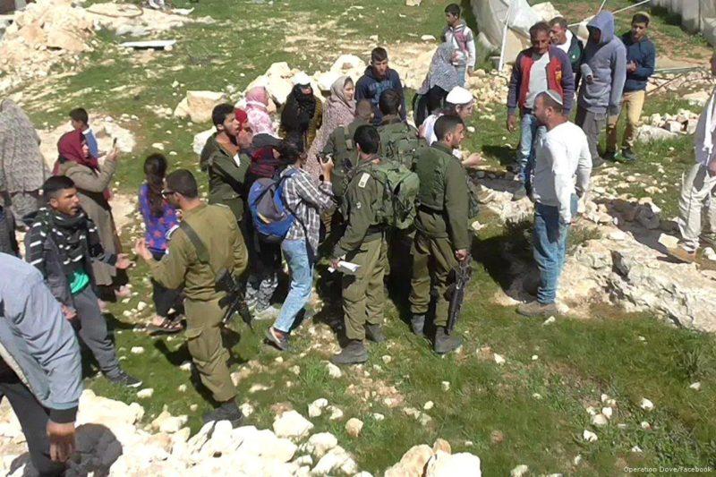 Serdadu Zionis berdiri di antara para pemukim ilegal Yahudi dan warga Palestina. Foto: Operation Dove/Facebook
