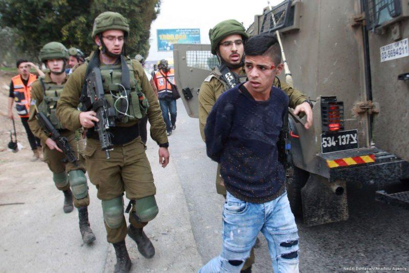 Gerombolan serdadu Zionis membawa remaja Palestina ke tahanan di Tepi Barat pada 20 Desember 2017. Foto: Nedal Eshtayah/Anadolu Agency