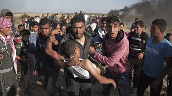 Demonstran Palestina menggotong seorang pria yang terluka karena ditembak serdadu Zionis saat demonstrasi. Foto: Khalil Hamra/AP