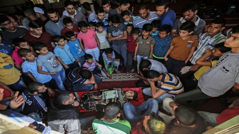 Para pelayat berkumpul mengelilingi jenazah seorang pria yang gugur oleh serdadu Zionis di perbatasan Gaza. Foto: AFP