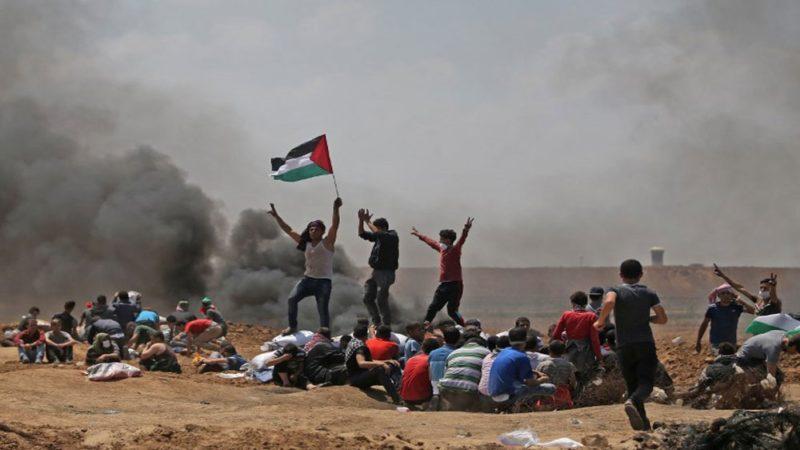 Warga Palestina mengibarkan bendera nasional mereka saat berdemonstrasi di dekat perbatasan dengan wilayh Palestina terjajah 1948 dan Jalur Gaza, di timur Jabalia. Foto: AFP