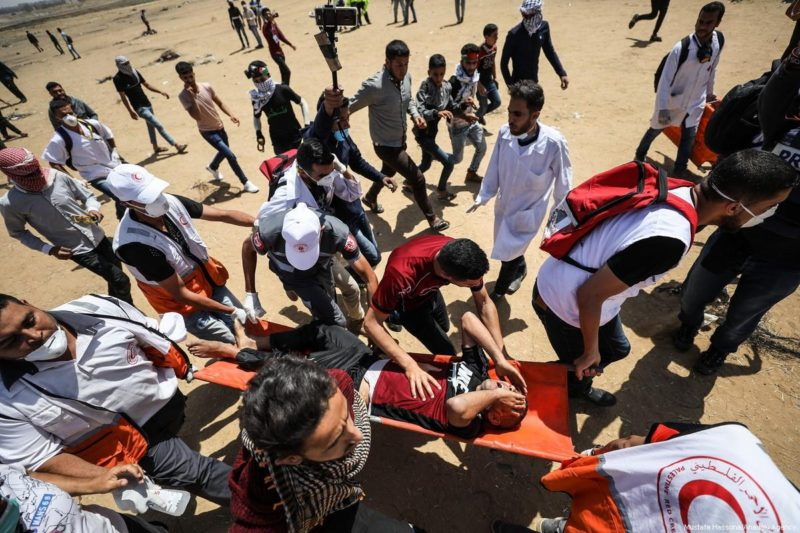 "Seorang demonstran Palestina yang terluka digotong oleh para anggota tim kesehatan setelah terluka akibat intervensi serdadu Zionis dalam demonstrasi ""Great March of Return"" di Khan Younis, Gaza, 11 Mei 2018. Foto: Mustafa Hassona/Anadolu Agency"
