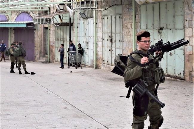 Serdadu Zionis memeriksa identitas tiga warga Palestina pada 21 Maret 2017, di Kota Tua Al-Khalil. Foto: Arsip Ma'an News Agency
