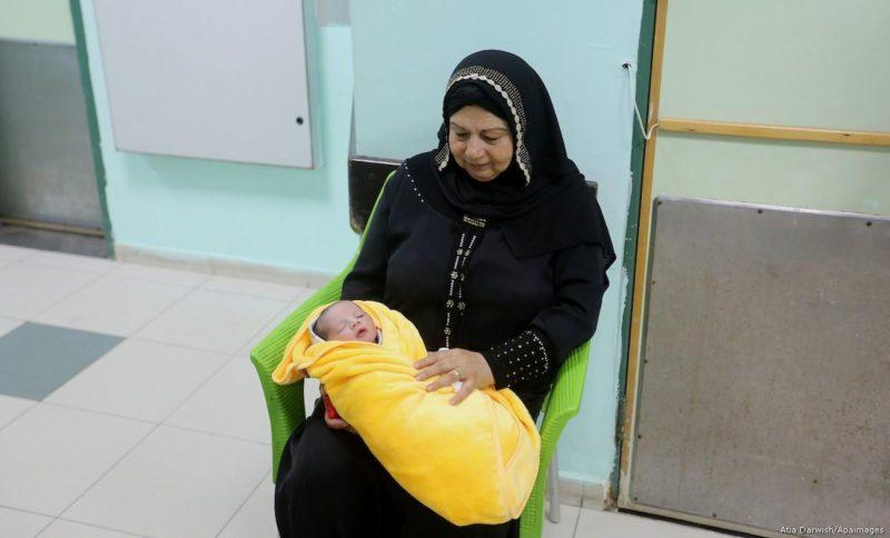 Wanita Palestina menggendong seorang bayi yang baru lahir, Rami Hamdallah, di RS Al-Shifaa, di kota Gaza pada 2 Oktober 2017. Foto: Atia Darwish/Apaimages