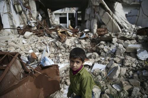 Seorang anak laki-laki berjalan di atas bangunan yang hancur di Ghouta Timur, Suriah. Foto: Daily Sabah