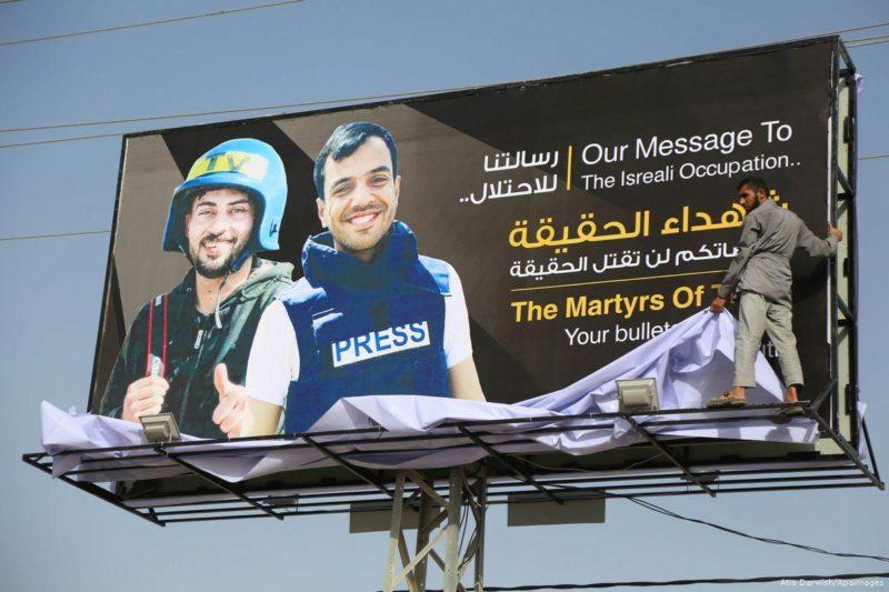 Warga Palestina berjalan di depan papan iklan yang didedikasikan untuk para wartawan yang tewas oleh serdadu Zionis di perbatasan Gaza-'Israel', di utara kota Gaza, pada 3 Mei 2018. Foto: Atia Darwish
