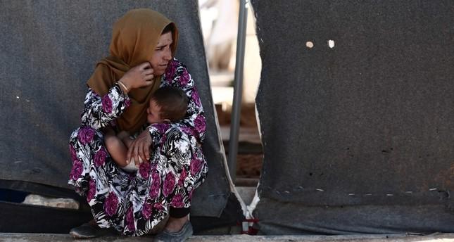 Seorang wanita sambil menggendong anak duduk di depan tenda di sebuah kamp untuk Muhajirin dari provinsi Idlib, di desa al-Ghadfa, tenggara Idlib pada 2 September 2018. Foto: AFP