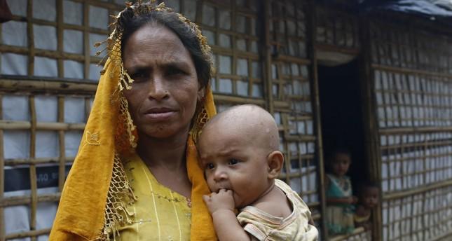 Seorang ibu Rohingya menggendong anaknya di sebuah kamp sementara di Teknuf, Cox's Bazar, 24 Agustus. Foto: Daily Sabah