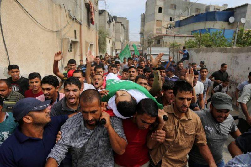 """Warga Palestina menggotong jenazah Hussein Fathi al-Raqab (28) yang syahid dibunuh serdadu Zionis dalam demonstrasi """"Great March of Return"""". Ia dimakamkan di Khan Younis, Gaza, pada 6 Oktober 2018. Foto: Ashraf Amra/Anadolu Agency"""