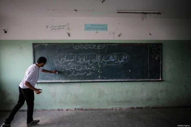 Guru Faris Hafez al-Sarasawi (12), menulis nama muridnya yang syahid itu di papan tulis. Foto: Ali Jadallah/Anadolu Agency