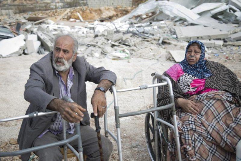 Basma Al-Rajabi dengan tabung oksigennya dan suaminya Muhammed Recebi hanya bisa menatapi reruntuhan bangunan setelah gerombolan serdadu Zionis menghancurkan rumah mereka dengan dalih tak berizin di kota Beit Hanina, Kota Tua, Baitul Maqdis Timur pada 6 November 2018. Foto: Mostafa Alkharouf/Anadolu Agency