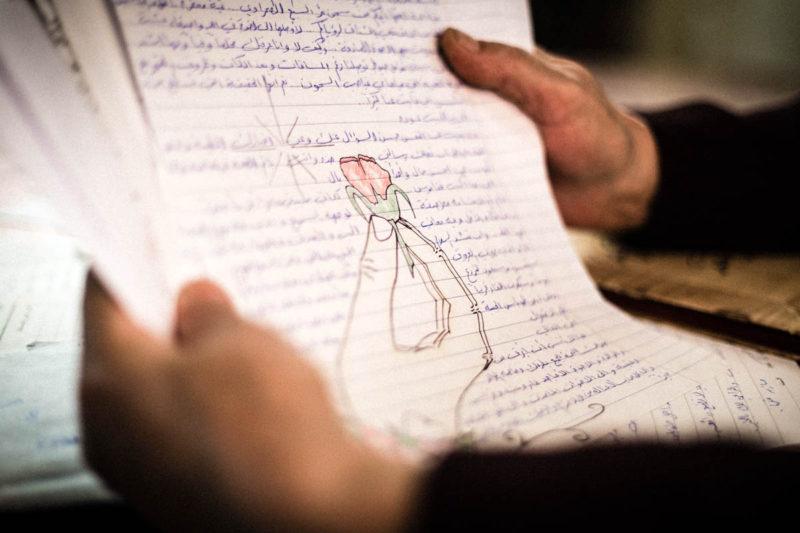 Di sela kunjungannya, Daraghmeh membaca surat bergambar mawar yang ditulis putranya dari dalam penjara. Foto: Alyona Synenko/ICRC