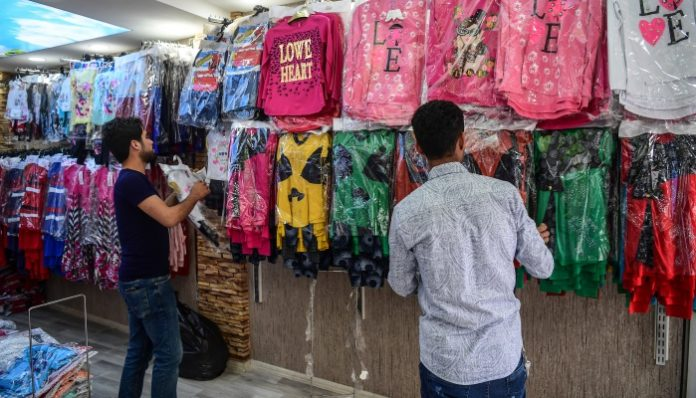 Pekerja Suriah membereskan pakaian untuk dipajang di sebuah toko pada 1 Mei 2018 di Gaziantep, di bagian barat daya Turki. Di kota Gaziantep, Turki, rumah bagi sekitar setengah juta Muhajirin Suriah yang melarikan diri dari perang di selatan perbatasan, ratusan bisnis Muhajirin Suriah berkembang baik bagi komunitas Muhajirin maupun negara tuan rumah mereka. Foto: Ozan Kose/AFP