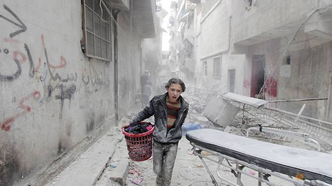 Seorang anak laki-laki berlari membawa barangnya setelah bom gentong dijatuhkan oleh pasukan yang setia kepada Presiden Suriah Bashar al-Assad di distrik al-Fardous, Aleppo, Suriah, 2 April 2015. Foto: Reuters/Rami Zayat/Foto Dokumentasi