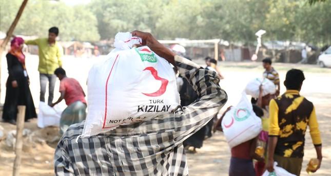 Seorang pria membawa karung berisi bantuan makanan yang didistribusikan oleh Bulan Sabit Merah Turki di sebuah kamp untuk Muslim Rohingya di Bangladesh. Foto: Daily Sabah