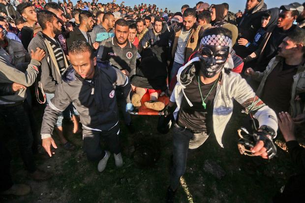 """Warga Palestina menggotong seorang wanita yang ditembak di kepala saat demonstrasi """"Great March of Return"""". Foto: MEE/Mohammed Asad"""