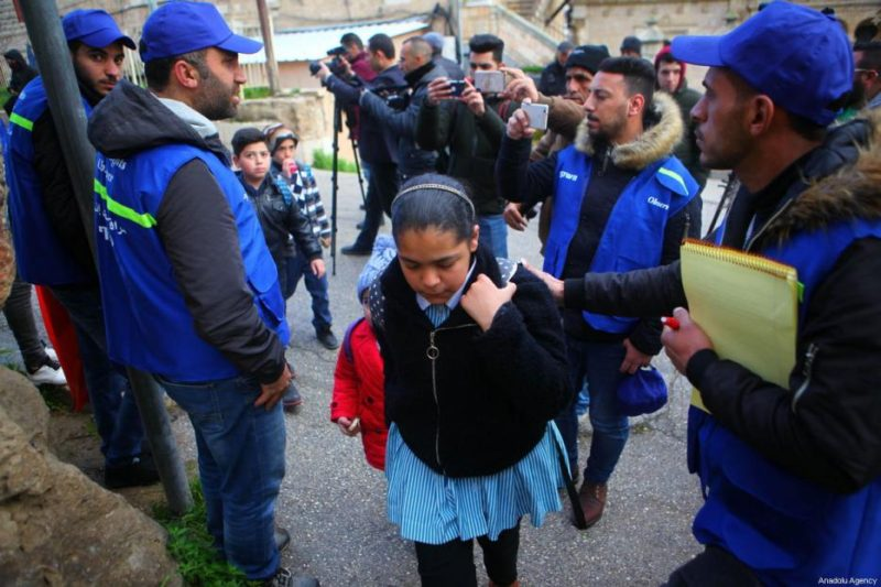 Aktivis YAS mendampingi anak-anak yang hendak ke sekolah di Al-Khalil, Tepi Barat, pada 10 Februari 2019. Foto: Mamoun Wazwaz/Anadolu Agency
