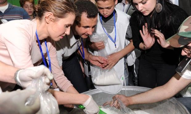 Bashar dan Asma al-Assad di pusat distribusi makanan di Damaskus. Foto: AFP