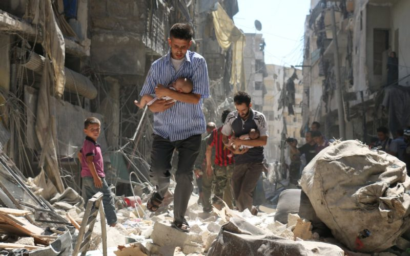 Dua lelaki Suriah mengendong bayi melewati reruntuhan bangunan setelah terjadinya serangan udara di kawasan Salihin di Aleppo. Foto: Ameer Alhalbi/AFP/World Press Photo Handout