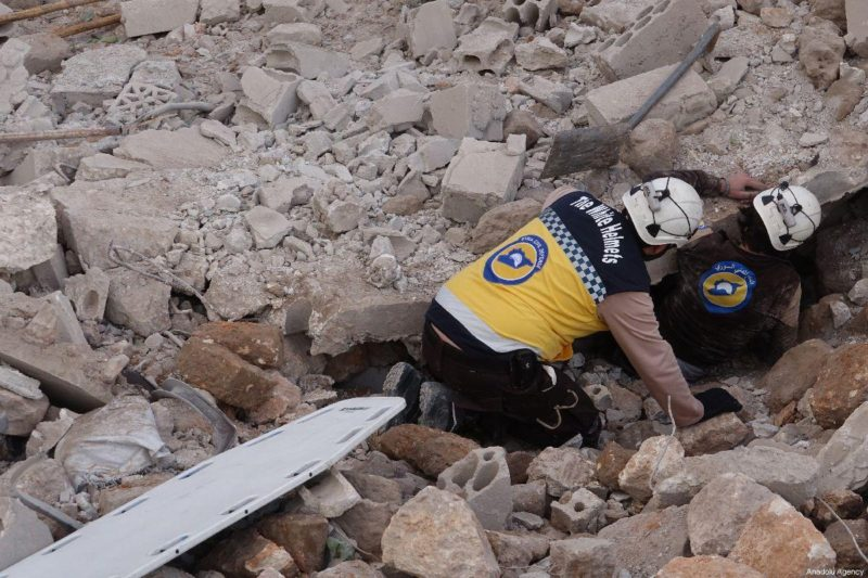 Para anggota pertahanan sipil melakukan operasi pencarian dan penyelamatan di bawah reruntuhan gedung-gedung yang hancur akibat serangan udara yang menghantam daerah pemukiman di zona de-eskalasi Idlib, Suriah, pada 22 Maret 2019. Foto: Hasan Muhtar/Anadolu Agency