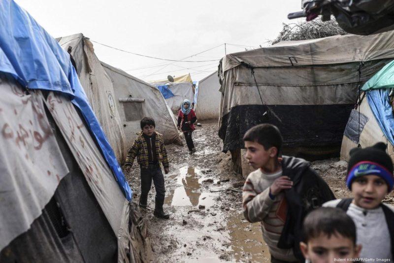 Anak-anak Suriah berjalan di lumpur setelah hujan deras mengguyur sebuah kamp pengungsi di Suriah pada 6 Februari 2016. Foto: Bulent Kilic/AFP/Getty Images