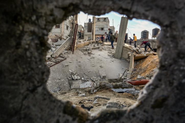 Warga Palestina berjalan melewati puing-puing gedung yang hancur akibat serangan udara 'Israel', Rafah, selatan Jalur Gaza, 5 Mei 2019. Foto: Abed Rahim Khatib/Flash90