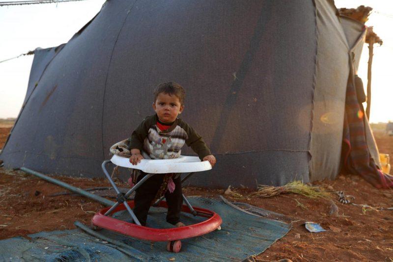Seorang bayi Suriah di luar tenda sebuah kamp untuk warga sipil yang melarikan diri dari pasukan pemerintah yang masuk ke provinsi Idlib yang dikuasai oposisi pada September 2018. Foto: AFP