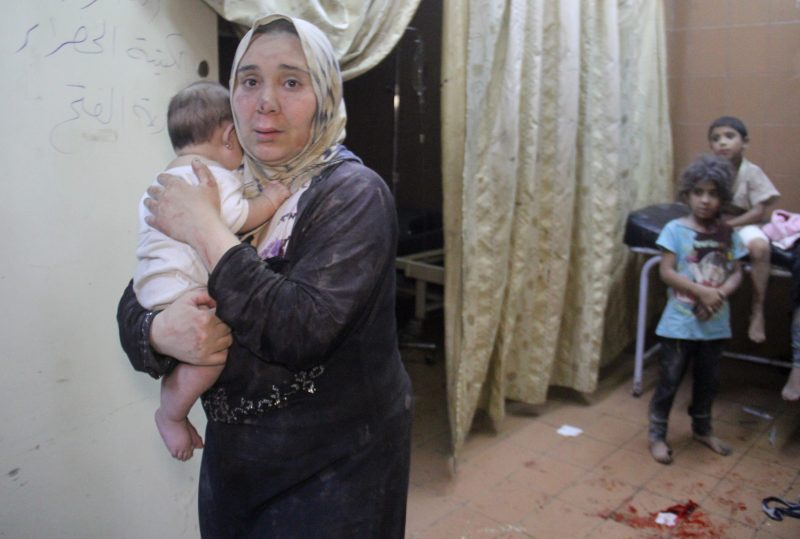 Seorang wanita Suriah menggendong bayi di dalam rumah sakit darurat setelah serangan dan pengeboman di kota Idlib barat laut yang dikuasai oposisi, pada 21 Juli 2016. Foto: AFP