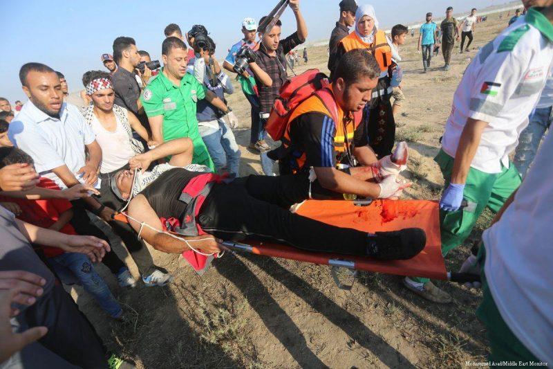 "Tenaga medis Palestina menolong seorang pria yang terluka setelah serdadu Zionis menyerang demonstran saat unjuk rasa ""Barisan Pulang ke Tanah Air"" (Great March of Return) di Gaza pada 14 Juni 2019. Foto: Mohammad Asad/Middle East Monitor"