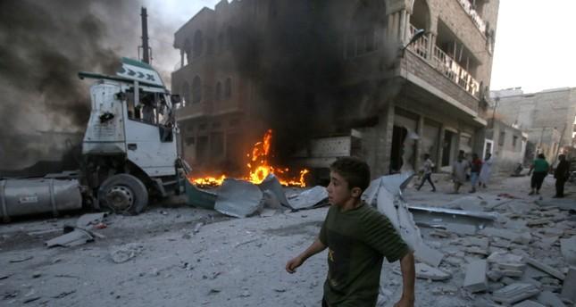 Seorang bocah lelaki berlari melewati api setelah serangan udara oleh pasukan rezim Assad di kota Maaret al-Numan di barat laut provinsi Idlib, Suriah, pada 28 Agustus 2019. Foto: AFP