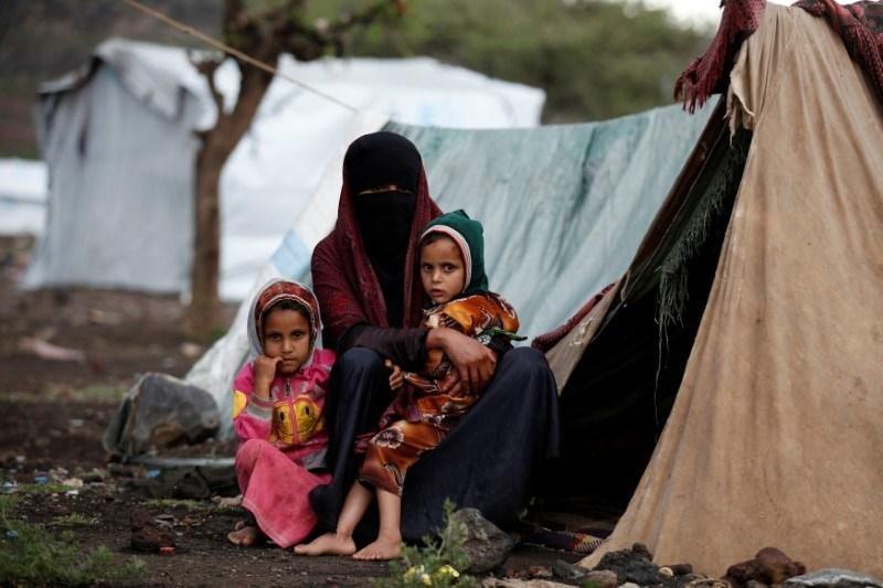 Seorang wanita dan kedua putrinya duduk di luar tenda mereka di sebuah kamp untuk pengungsi internal dekat Sanaa, Yaman, pada 15 Agustus 2016. Foto: Reuters/Khaled Abdullah