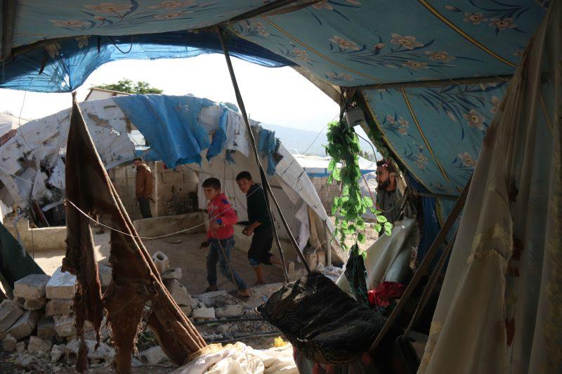 Anak-anak berjalan melewati tenda-tenda kamp yang rusak di Qah, Suriah. Foto: MEE/Muhammad Alhosy