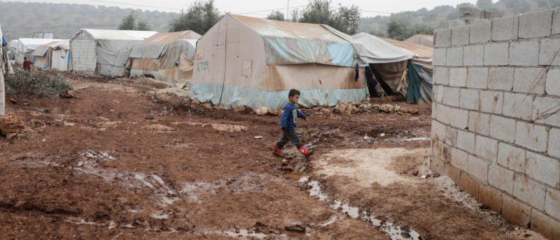 Seorang anak lelaki Suriah berjalan melewati lumpur, di antara tenda-tenda keluarga pengungsi di Idlib. (Abdullah Hammam)