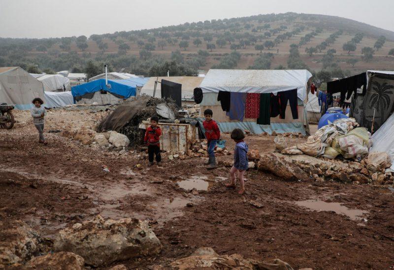 Anak-anak berjalan di lumpur setelah hujan lebat di Desa Qah, pinggiran Idlib utara. (Abdullah Hammam)