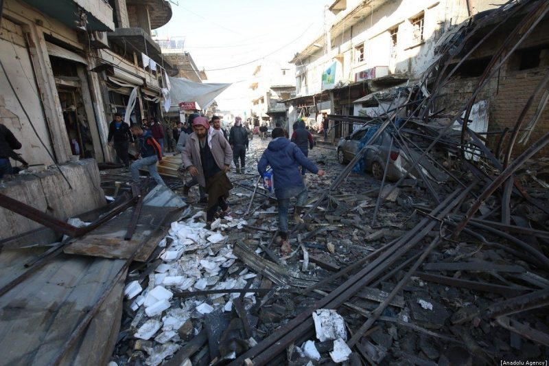 Warga lokal melintas di lokasi yang dihantam serangan udara rezim Assad, di Desa Binnish, di Idlib, Suriah pada 11 Januari 2020. Setidaknya 17 warga sipil dilaporkan tewas [Izzeddin Idilbi / Anadolu Agency]