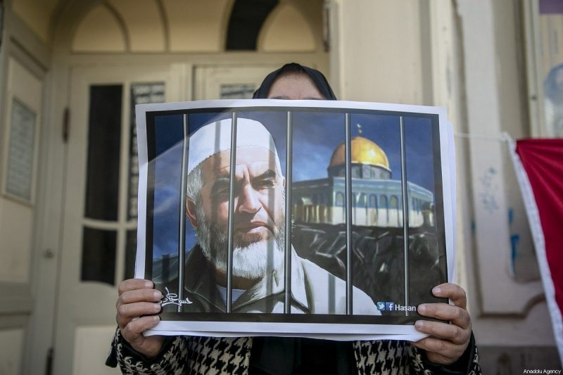Sekelompok warga Tunisia memegang poster ketika mereka berkumpul memprotes keputusan pengadilan 'Israel' yang menghukum Syaikh Raed Salah hingga 28 bulan penjara, di depan teater kota di Tunis, Tunisia pada 21 Februari 2020. [Yassine Gaidi – Anadolu Agency]