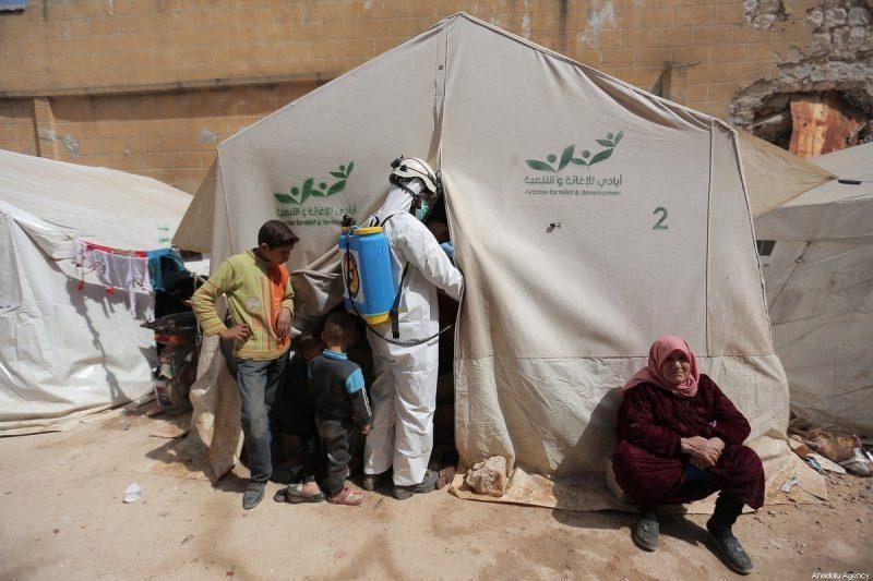 Anggota Pertahanan Sipil Suriah (White Helmets) mendisinfeksi bangunan dan tenda tempat keluarga tinggal bersama sebagai langkah pencegahan terhadap wabah Covid-19 di Idlib, Suriah pada 24 Maret 2020 [Muhammed Said - Anadolu Agency]