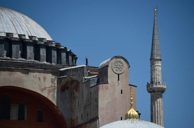 Seorang petugas polisi Turki berjalan dengan senjatanya di area kubah saat muazzin menyerukan shalat Jumat di menara Masjid Agung Ayasofya di Istanbul, Turki, 24 Juli 2020. (AP)